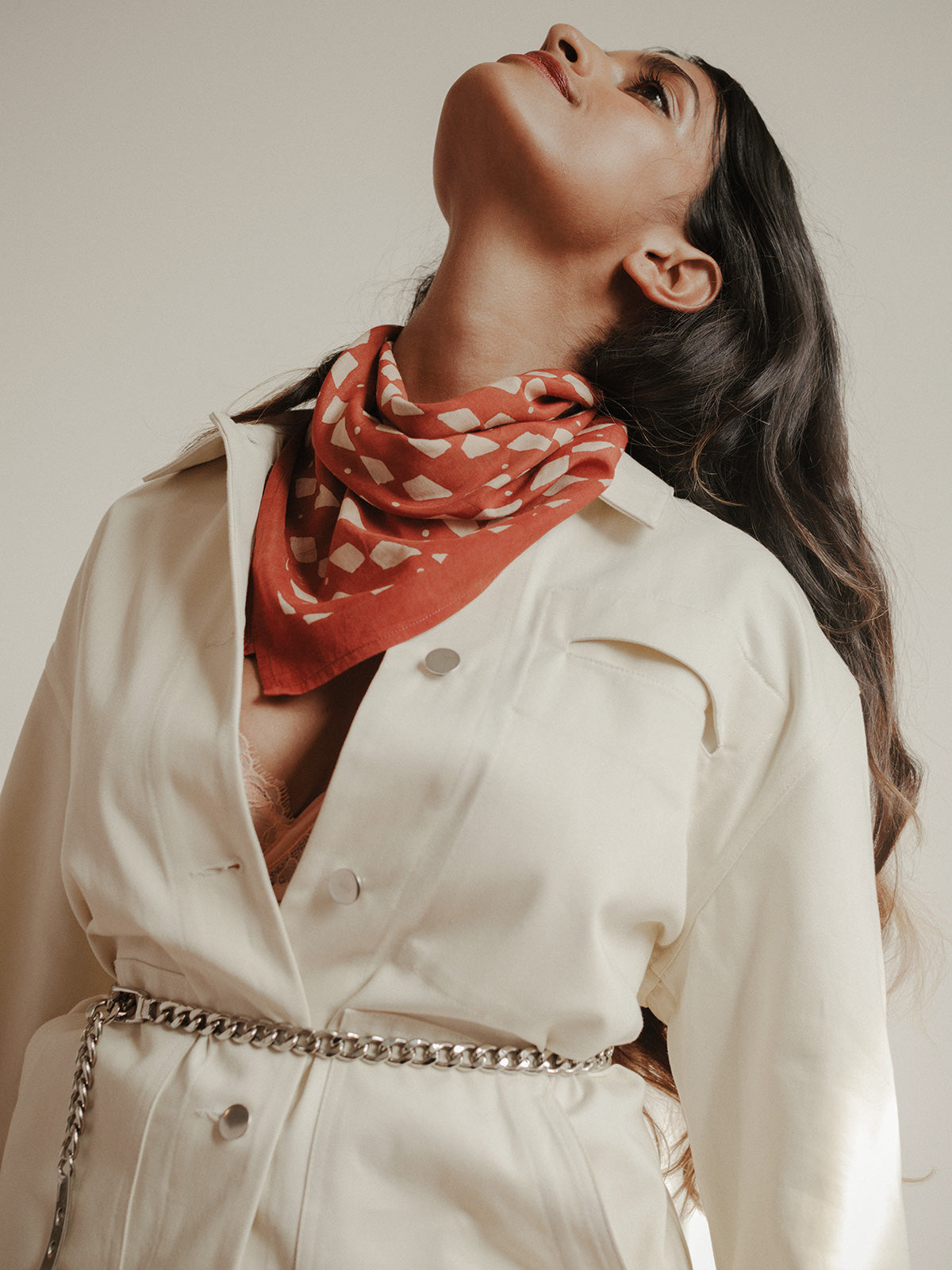Deep earthy red block printed bandana scarf by SUNDAY/MONDAY. Worn around neck with a cream jacket for fall.