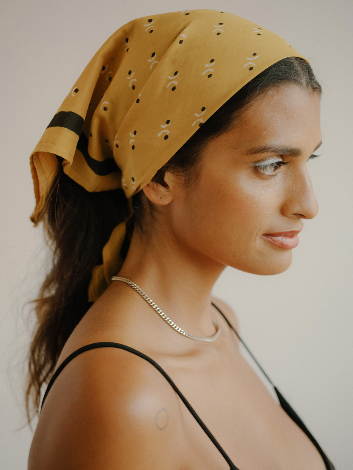 SUNDAY/MONDAY's Fermata bandana wrapped around hair. Block printed mustard yellow bandana.