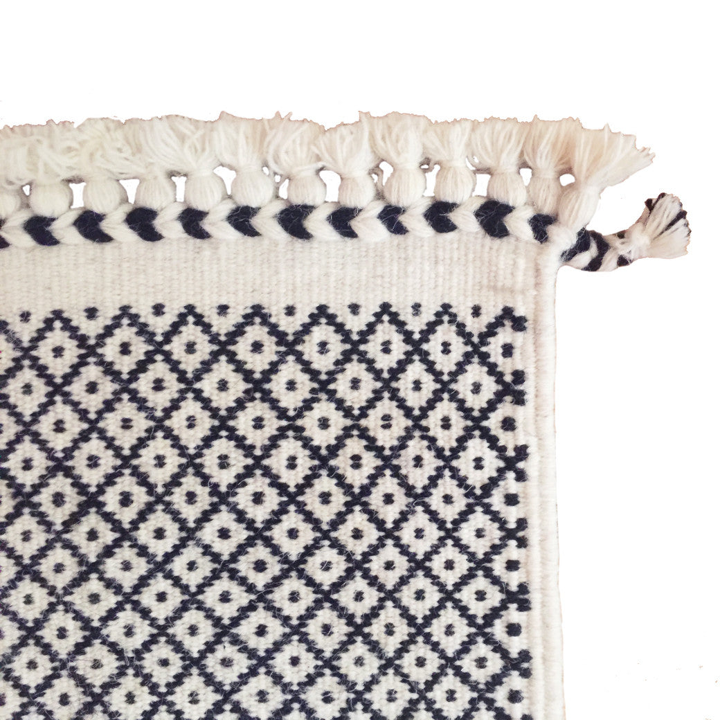 SUNDAY / MONDAY Handwoven 100% Wool Indian Flatweave Rug, Rann in White, Black and white wool area rug made in tribal indigenous lattice diamond miri braid tassel.  Handmade in Kutch, Gujarat