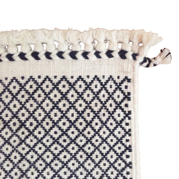 SUNDAY / MONDAY Handwoven 100% Wool Indian Flatweave Rug, Rann in White, Black and white wool area rug featuring tribal indigenous lattice diamond miri braid tassel.  Handmade in Kutch, Gujarat