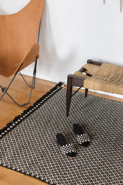 Handwoven black and white wool area rug with a geometric motif.