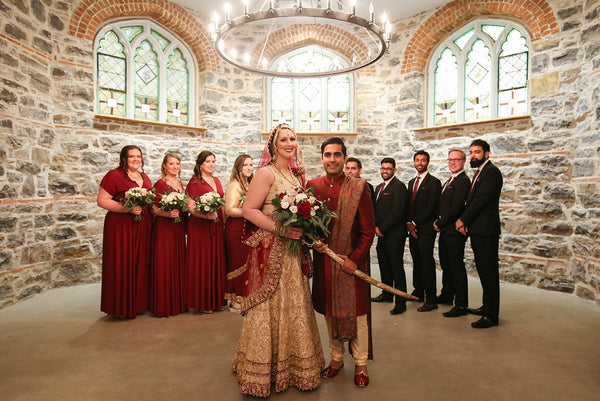 Stephanie and Subhir pose for portraits with their wedding party on their wedding. Brdesmaids are wearing Henkaa Sakura Convertible Bridesmaid Dresses in Burgundy Wine.
