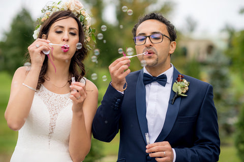Henkaa A Bride's Story: Diana & Jas. Bride and groom blowing bubbles on wedding day. Flower crown.