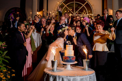 Henkaa A Bride's Story: Diana & Jas. Bride and groom kiss over wedding cake. Guests with sparklers.