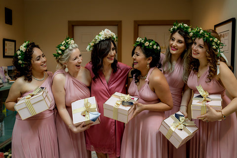 Henkaa A Bride's Story: Diana & Jas. Bride and bridesmaids exchanging bridesmaid gifts in pink silk bridal robes and flower crowns.