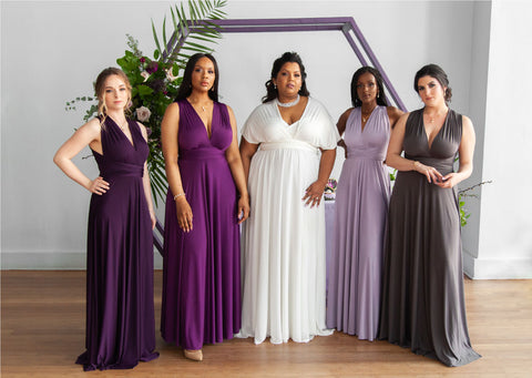 Models line up in Henkaa Sakura Convertible Dresses in colours: Eggplant Purple, Plum Purple, Pure Ivory, Dusty Purple and Charcoal Grey.