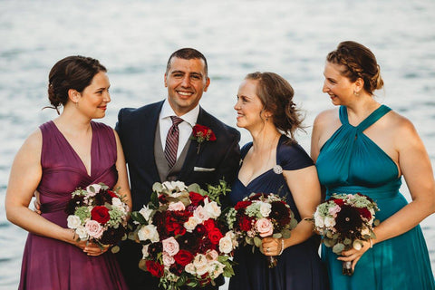 Ayad Sbeyti poses with the bridesmaids who are wear Henkaa Sakura Convertible Maxi Dresses in the colours Plum Purple, Navy Blue and Turquoise Teal.