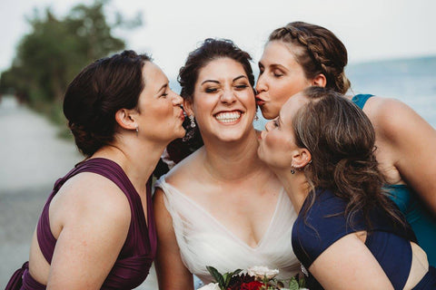 Jacqueline Sbeyti gets kissed on the cheeks by her bridesmaids who are wearing Henkaa Sakura Maxi Dresses in Plum Purple, Navy Blue, and Turquoise Teal.