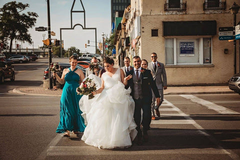 Jacqueline Sbeyti and Ayad Sbeyti lead the wedding party across the street during their wedding portraits.