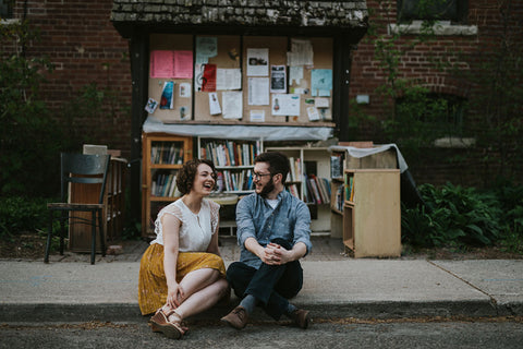 Averie MacDonald and Bled Celhyka pose for engagement photos in front of a bookstore.