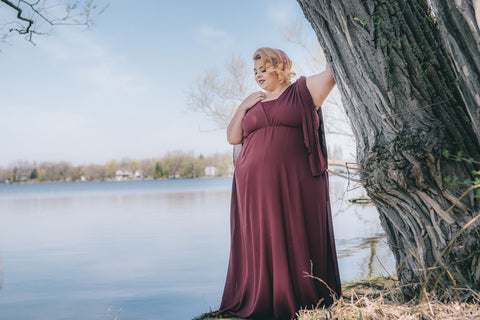 Plus-size model Jewelz Mazzei stands next to tree in Henkaa Burgundy Wine Daffodil Chiffon convertible dress for fall/winter 2018 wedding collection photoshoot