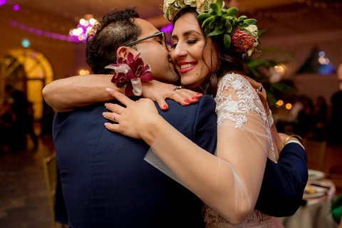 Henkaa A Bride's Story: Diana & Jas. Multicultural bride and groom embrace in a hug. Bride in flower crown and corsage.