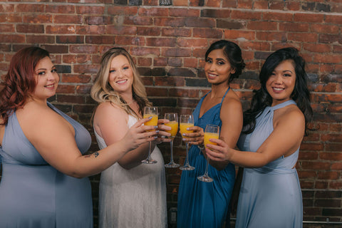 Bridesmaids and bride cheers with mimosas. Bridesmaids are wearing Henkaa Dusty Blue and Light Sky Blue Sakura Maxi infinity dresses and Slate Blue Ivy Maxi convertible dresses. Bride is wearing the Sakura Lace convertible wedding dress.