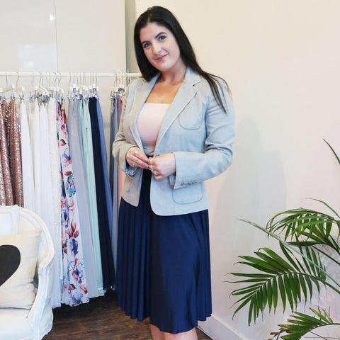 Business women with black straight hair wearing Henkaa navy blue knee length infinity dress as skirt with Henkaa nude champagne bandeau and light blue blazer.