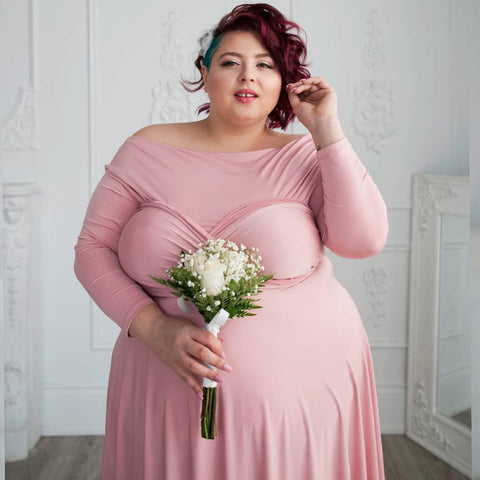 Plus-size model Jewelz Mazzei in wears a Henkaa Dusty Rose Iris Midi convertible dress and looks into the camera.