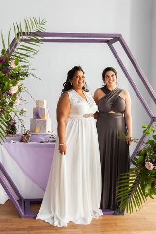 Models connect in Sakura Chiffon Convertible Wedding Dress and Charcoal Grey Sakura Maxi Convertible Dress in front of a hexagon shaped arch.