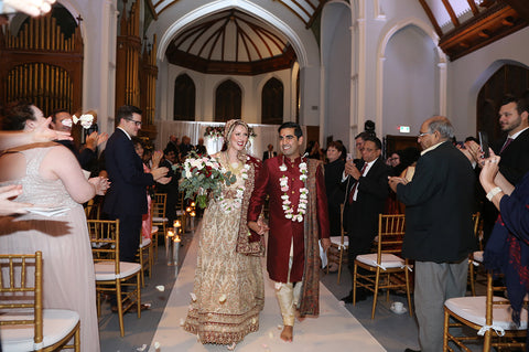 Stephanie Rochefort and Subhir Uppal walk down the aisle hand-in-hand after their multicultural wedding at allsaints Event Space in Ottawa Ontario, Canada.