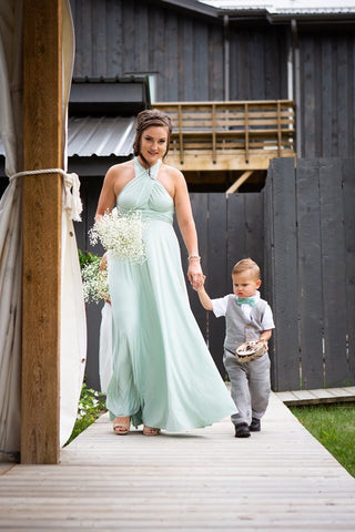 A bridesmaid walks down the aisle in a Mint Green wedding dress, the Henkaa Sakura Maxi Convertible Dress, holding Ashley's son's hand.