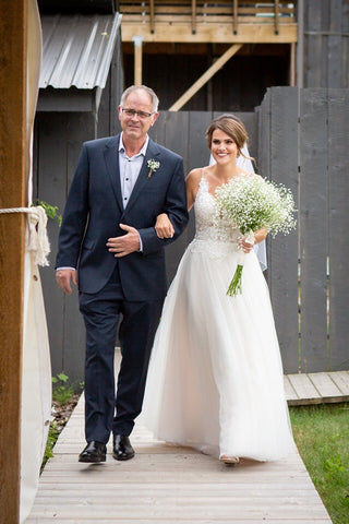 Ashley's father walks her down the aisle, Ashley holds a large bouquet of Baby's-breath.