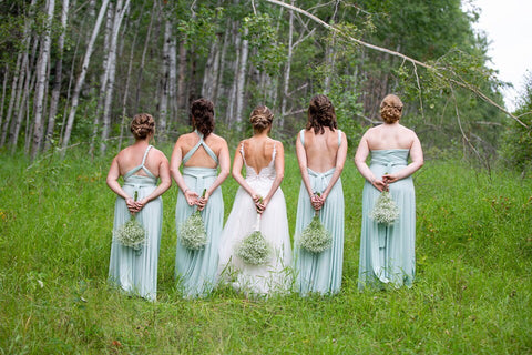 Ashley and her bridesmaids stand in a field holding Baby's-breath bouquets behind their backs. Bridesmaids are wearing Henkaa Convertible Dresses in Mint Green.