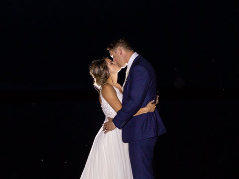 Ashley and Jordan share an intimate kiss on a dock at the waters edge at the end of their mint green wedding night.