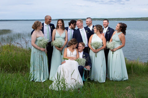 Ashley and Jordan pose with their wedding party at the lakes edge, bridesmaids are wearing Henkaa Sakura Maxi Convertible Dresses in Mint Green.