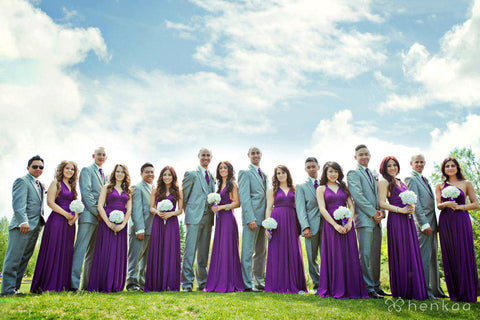 Wedding party wearing Henkaa Plum Purple Sakura Maxi Convertible Dresses and matching Henkaa ties and holding white flower bouquets