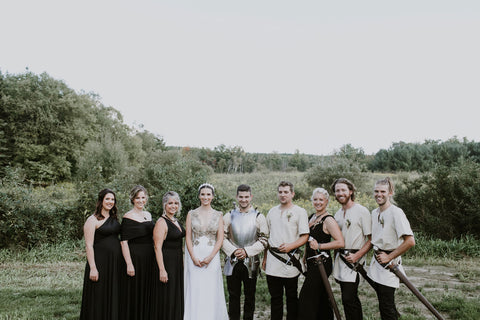 Alex and Lauren Melnik stand with the bridal party and groomsmen. Bridesmaids in Henkaa Night Black Sakura Maxi infinity dresses and groomsmen in traditional medieval clothing with swords.