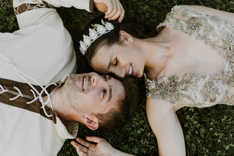Alex and Lauren Melnik lay on the grass as husband and wife during tasteful medieval themed wedding featured on the Henkaa infinity dress blog.