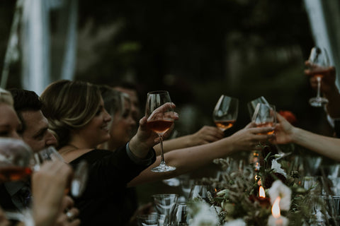 Attendees at a medieval themed wedding cheers with their glasses over harvest table.