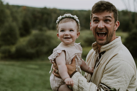 Alex Malnik husband in medieval outfit holding baby Mars Melnik during wedding. Featured on Henkaa A Brides Story: Lauren & Alex on the Henkaa infinity dress blog.