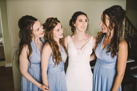 Rachel embraces her bridal party who are wearing Dusty Blue Henkaa Sakura Maxi Convertible Dresses.