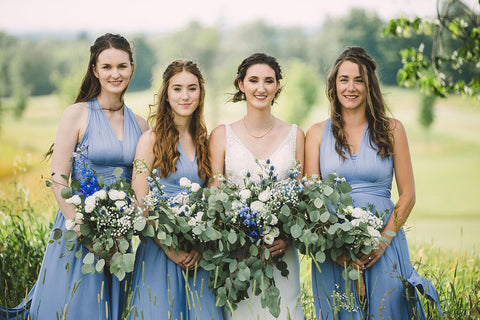 Rachel poses with her bridal party who are wearing Dusty Blue Henkaa Sakura Maxi Convertible Dresses.