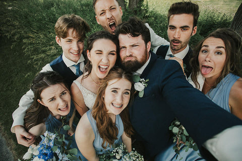 Rachel and Joel embrace their wedding party for a photo, bridesmaids are wearing Dusty Blue Henkaa Sakura Maxi Convertible Dresses.