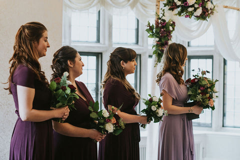 Averie's three bridesmaids and maid of honour stand holding bouquets during the wedding ceremony. Bridesmaids are wearing Henkaa Sakura Maxi Convertible Dresses in Eggplant Purple and Dusty Purple.