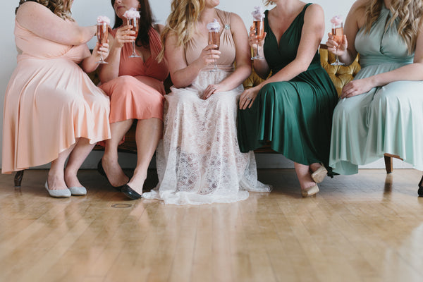 5 women raising glasses at a bridal party - add the party to the bridal checklist for your wedding day.