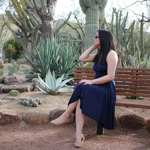 Henkaa's Managing Director Sonia Dong sits in an Arizona park in front of cacti wearing her Navy Blue Sakura Midi dress for National Dress Day.