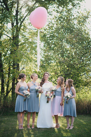 A bridal party stands arms around each other with pink heart balloon. Bridesmaids are wearing Henkaa Silver Grey Sakura Midi infinity dresses.