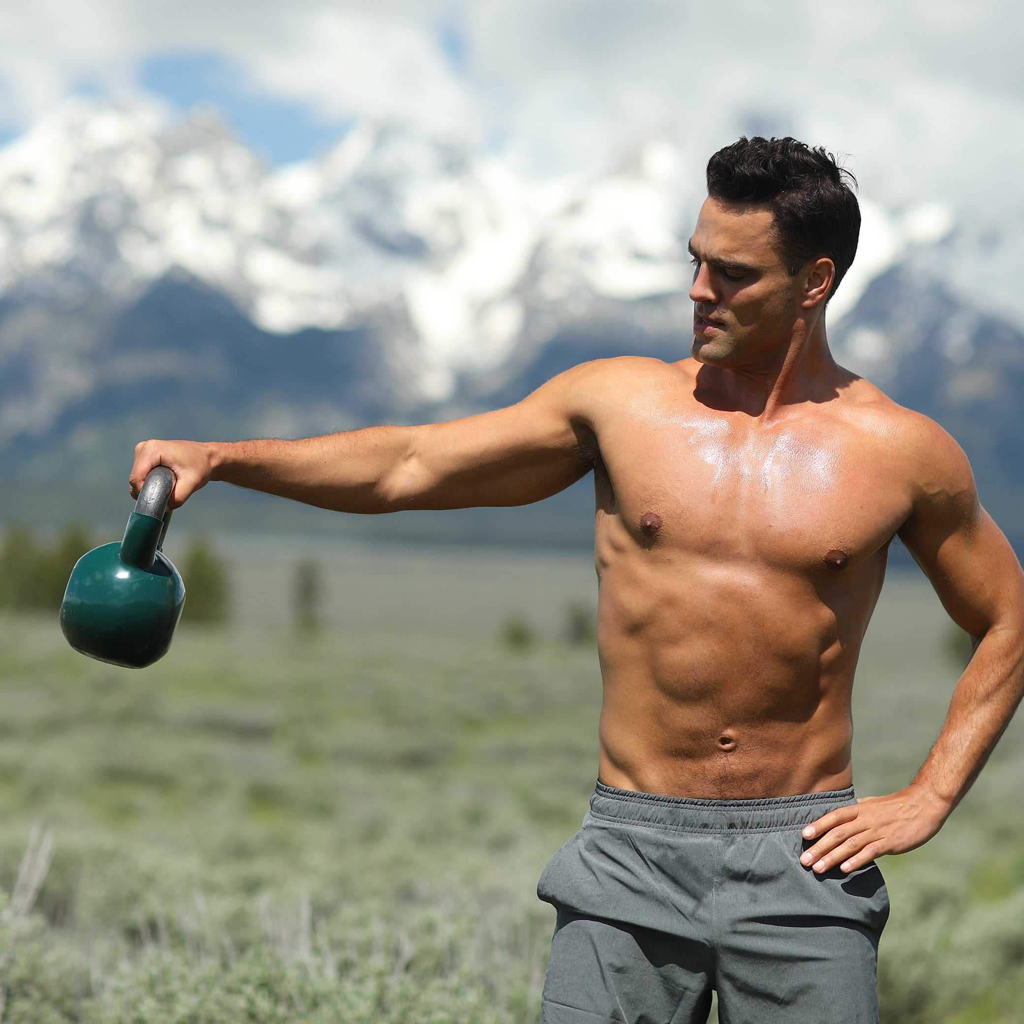Matthew Konsmo using a kettle ball to do shoulder raises in the mountains