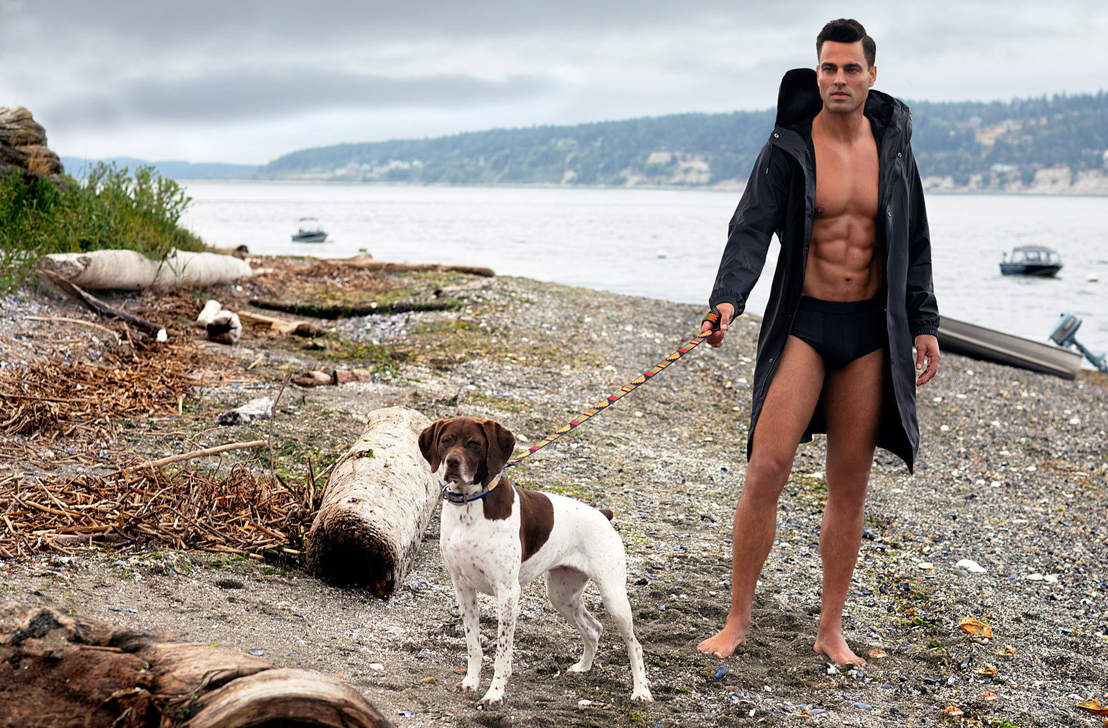 Matthew Konsmo modeling underwear in raincoat with dog on a leash while on the rocky beach in Camano Washington