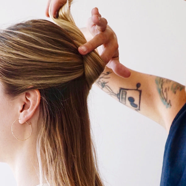Place a finger to the left side of the twist, and spin hair around finger to making a bun