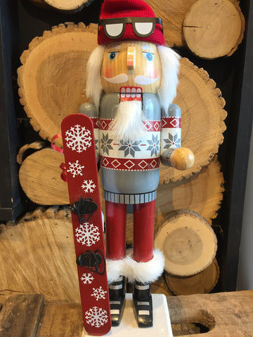 Nutcracker dressed in festive Christmas outfit holding his snowboard