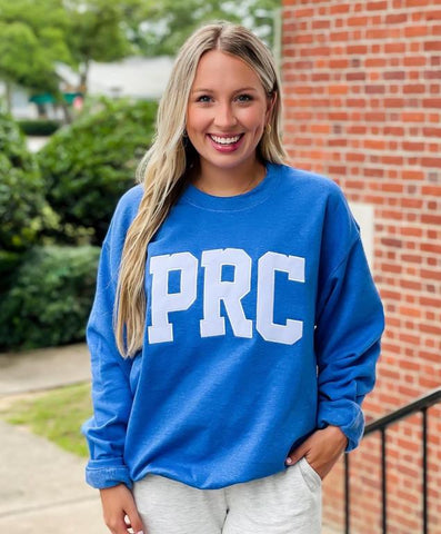 blonde woman in a blue sweatshirt that says PRC