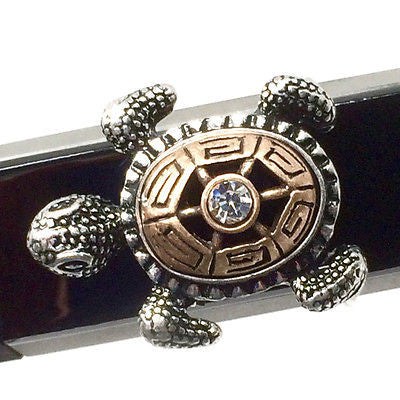 Closeup of Fitband Bling Sea Turtle two-tone gold and silver metal and rhinestone charm on Fitbit Alta band