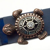 Closeup of Fitband Bling Sea Turtle two-tone silver and copper metal and rhinestone charm on Fitbit Flex band