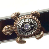 Closeup of Fitband Bling Sea Turtle two-tone silver and gold metal and rhinestone charm on Fitbit Alta band