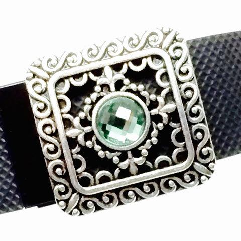 Closeup of silver filigree with green rhinestone center fitness band charm on a Fitbit Charge HR