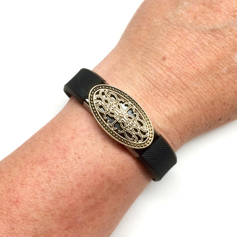 Large gold filigree oval bling accessory on a Fitbit Alta band