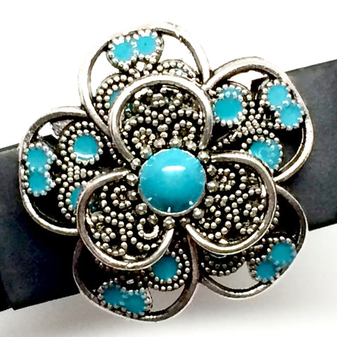 Closeup of silver filigree flower with turquoise enamel accents charm on Fitbit Flex band
