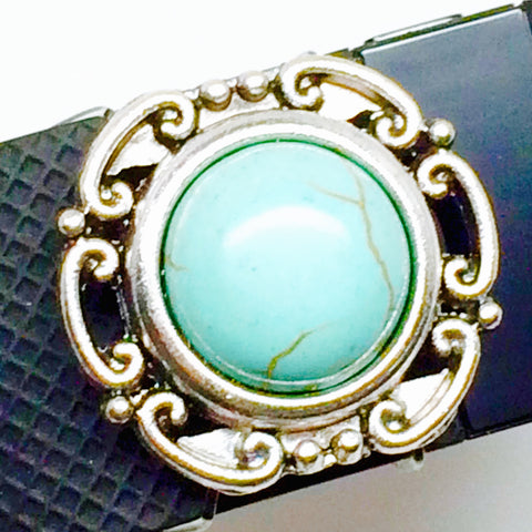 Closeup of scrolled silver setting with faux turquoise center accessory on Fitbit Charge HR band